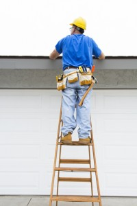 Man on ladder inspecting roof